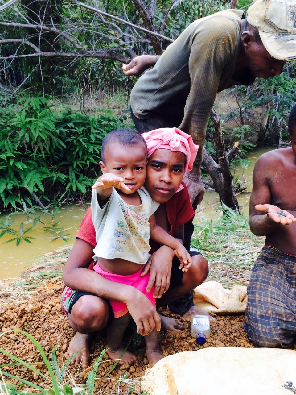 Malgas édesanya a gyermekével egy zafírbánya közelében, mellettük zafírválogatás folyik (Fotó: Szabó Nóra)