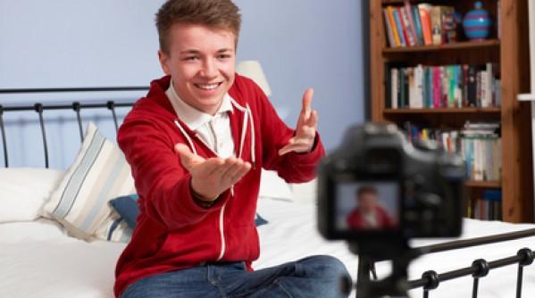 Teenage Boy Recording Video Of Himself In Bedroom
